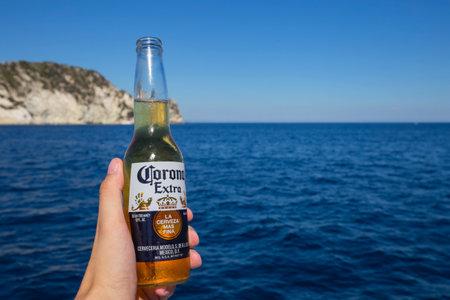 ZAKYNTHOS, GREECE - August 1, 2017: Corona beer bottle in hand on the sea