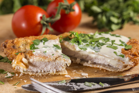 Pork schnitzel with white sauce and parsley on wooden cutting board Foto de archivo - 92943331