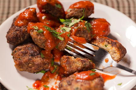 Eating fried meatballs made from pork and beef meat with tomato sauce and herbs on plate