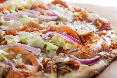 Close up of kebap pizza made with minced meat, cabbage, tomato and garlic sauce
