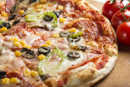 Close up of Italian Capriciosa pizza made with salami and vegetables Stock Photo