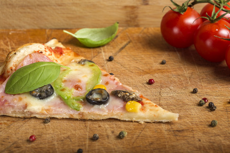 Slcae of Italian Capriciosa pizza made with salami and vegetables on wooden background Standard-Bild - 94514117