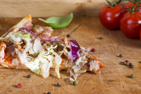 Slace of kebap pizza made with minced meat, cabbage, tomato and garlic sauce on wooden background Standard-Bild - 94506675