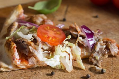 나무 배경에 다진 된 고기, 양배추, 토마토와 마늘 소스로 만든 kebap 피자의 Slace
