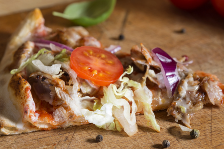 Slace of kebap pizza made with minced meat, cabbage, tomato and garlic sauce on wooden background