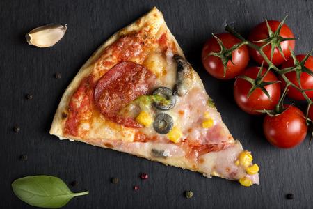 토마토와 허브와 다크 슬레이트에 이탈리아 카프리시 오사 피자 조각
