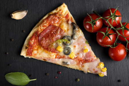 Slice of Italian Capriciosa pizza on dark slate with tomatoes and herbs