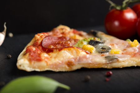 Close up of Slice of Italian Capriciosa pizza on dark slate with tomatoes and herbs