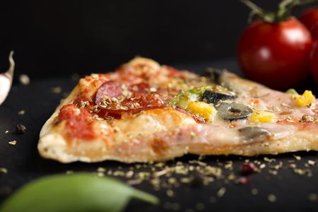 말린 오레가노와 다크 슬레이트에 이탈리아 Capriciosa 피자 조각 닫습니다