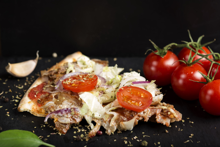 Slace of kebap pizza made with minced meat, cabbage, tomato and dried oregano on dark slate
