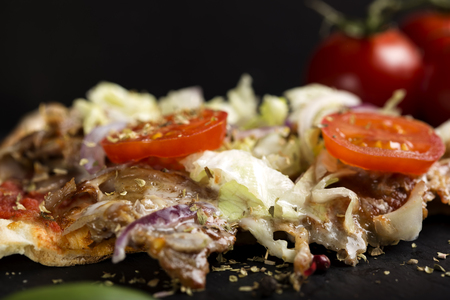 Close up of Slace of kebap pizza with dried oregano on dark slate Standard-Bild - 94506678
