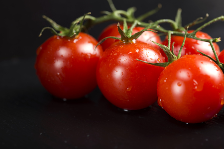 Bunch of cherry tomatoes with water drops on dark slate background