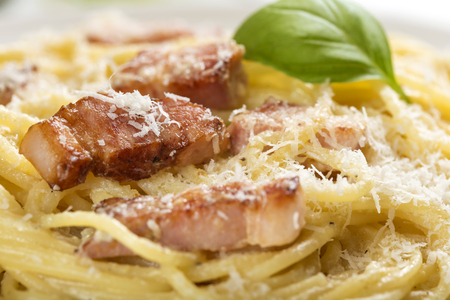 Plate with traditional Italian pasta Carbonara with grated parmesan and basil