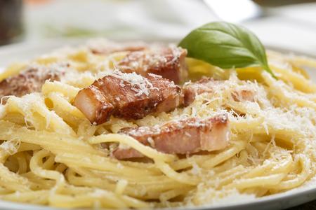 Platte mit traditioneller italienische Pasta Carbonara mit geriebenem Parmesan und Basilikum Standard-Bild - 94988595
