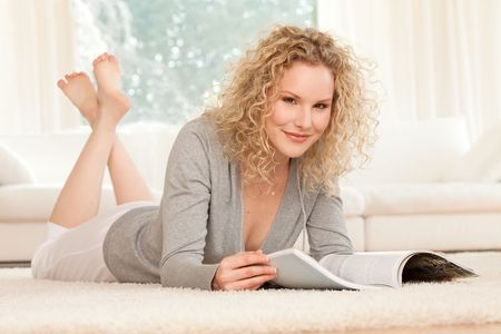 woman is lying on carpet and smiles while reading magazine photo