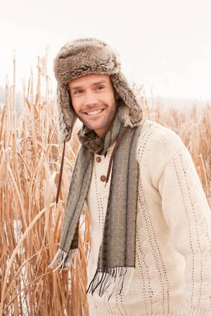 man standing outside in field in winter smiling photo