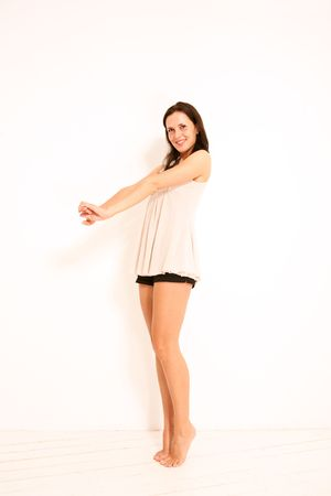 on tiptoes: attractive young woman infront of white background on tiptoes