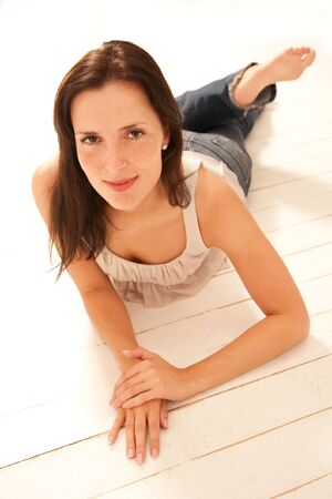 attractive young woman is lying on bright parquet flooring and smiles photo