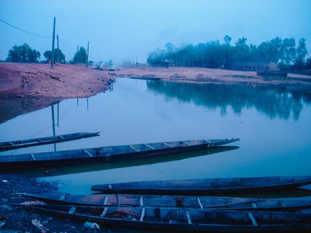 Fishing boats on the Niger River at sunset. boats used for traditional fishing in central africa. Stock Photo