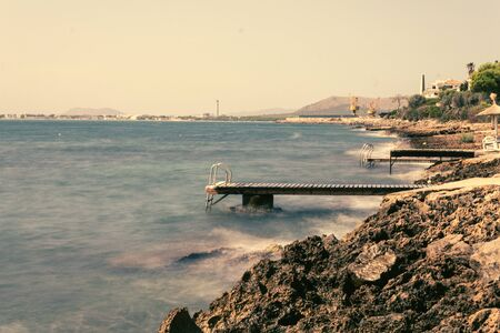 Alcanada beach with wooden ports overlooking the port of Alcudia. Sea enraged against the wooden port.