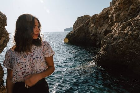 Adventurous young latin woman looking sideways on the sea rocks. Woman on cliff, with the sunset. Jovial near the sea on vacation in the Mediterranean with turquoise blue water.