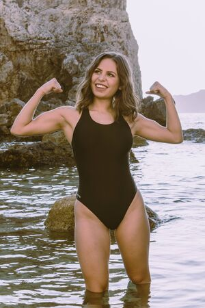 Young latin woman proud of her strong body. Fit girl showing her strong arms in the water. concept of being proud of your body, and displaying it on the beach. Woman in black swimsuit on the rocks.