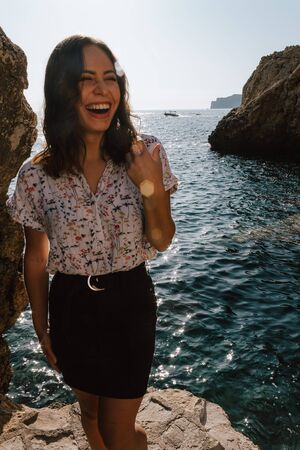 Young latin woman smiling near the sea with floral shirt. Jovial near the sea on vacation in the Mediterranean with turquoise blue water.