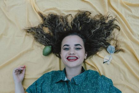 Young woman lying on yellow cloth as background. With curly brown hair. 스톡 콘텐츠