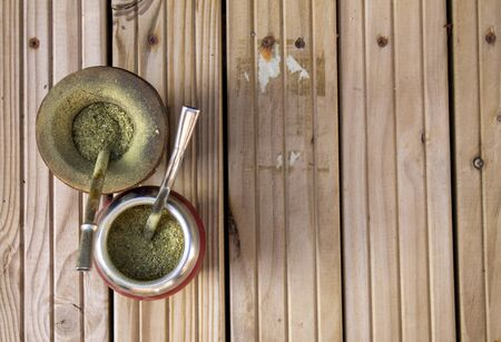 Mate Herbs Drink traditional from Argentina, Straw. With Calabash on wooden table.