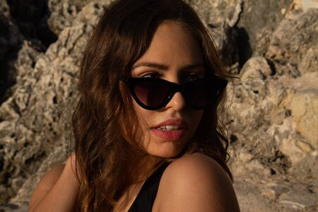 Portrait of young hipster woman with sunglasses enjoying summer. Autumn is approaching with good temperatures. autumnal beach. Stock Photo