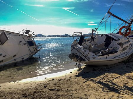Several boats stranded on the beach after a storm. On a sunny day with few clouds.