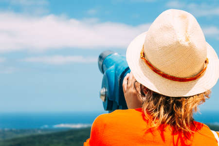 A Girl in a straw hat looks through city binoculars. Concept of travel.