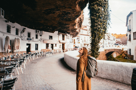 Young female tourist with a backpack is locking above in a small spain village that is build into a rock. 写真素材