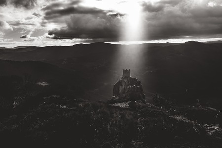 Lightbeam shining on medieval tower ruins built on a rock