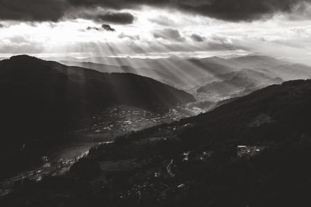 Lightbeams enlighten a valley in the French Alps on a cloudy day (Vestiges du Chateau de Rochebonne, Saint-Jean-Roure, France).