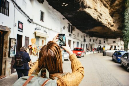 Woman photographing the overhanging rocky cliff