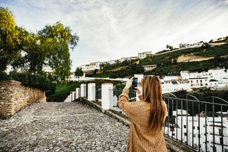 Young woman photographing a narrow street