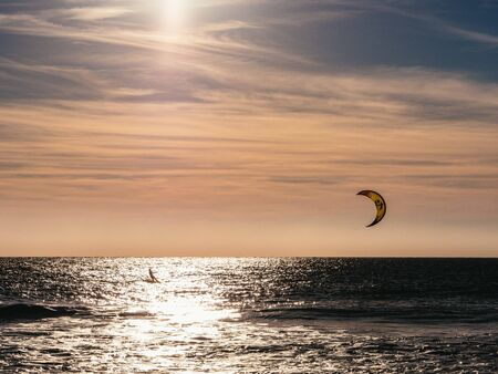 Lone kite surfer surfing at sunset