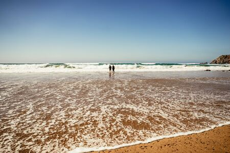 Two people walking in shallow surf along a beach