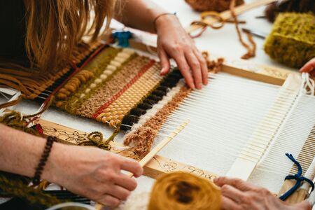 Femme essayant de tisser une tapisserie