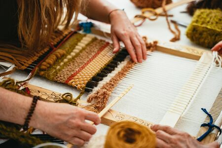 Woman trying her hand at weaving a tapestry