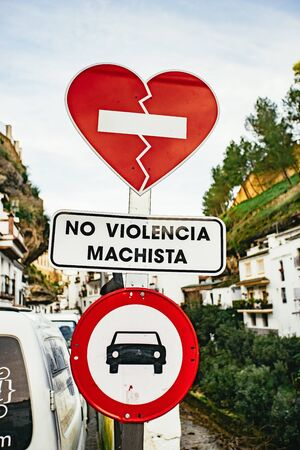 Road sign in Setenil de las Bodegas, Andalusia, Spain against male violence with a taped brown red heart, parking sign for vehicles