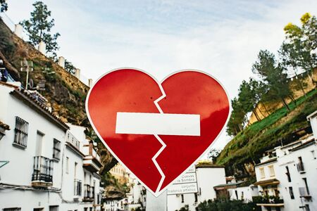 Red heart road sign in Setenil de las Bodegas, Andalusia, Spain with rows of whitewashed houses under steep cliffs 版權商用圖片