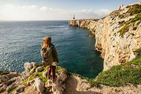 Woman looking across deep blue ocean next to cliff Imagens