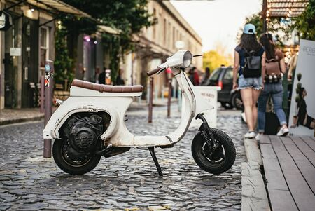 Old small white scooter parked in a cobbled street