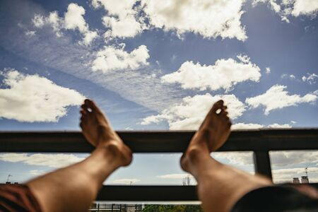 First Person POV of a man with feet up Stock Photo