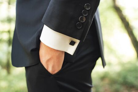 Side view of men in black suit. Close up of hand in pocket. Black square cufflinks on white shirt sleeves. Outdoor background.