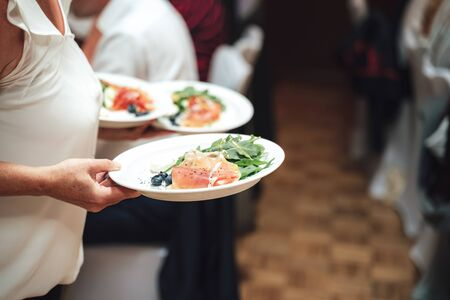 Woman carrying white plates with light snack. Slices of ham, garden rocket and blueberries. Celebration, party, birthday or wedding concept.