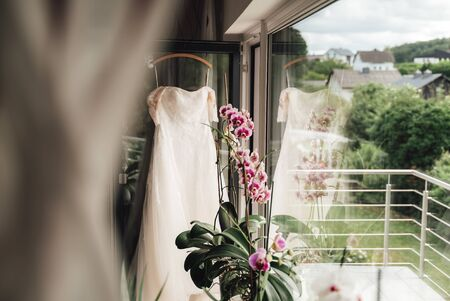 White wedding dress on hanger hanged on balcony door. Semi-reflected dress in large window. Colorful blooming orchid flower.