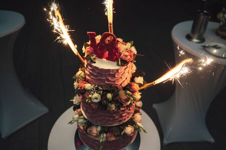 Close up of marriage cake with fireworks. Lettering love on top of cake. Celebration and wedding day concept.